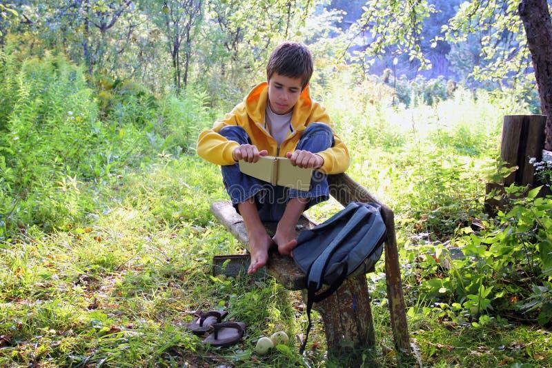 Teen boy reading a book stock photo