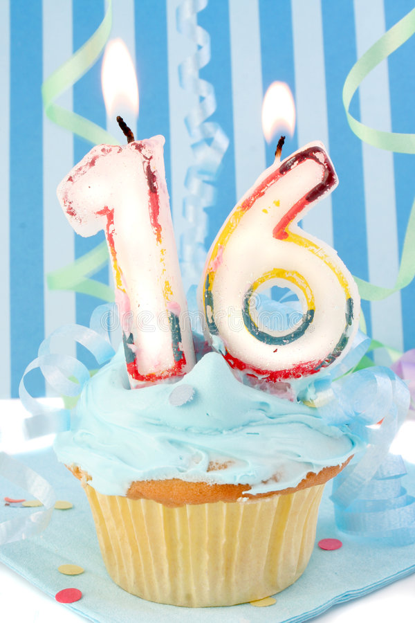 Teen boy's sixteenth birthday. Teenagers sixteenth birthday cupcake with blue frosting and decorative background royalty free stock photo