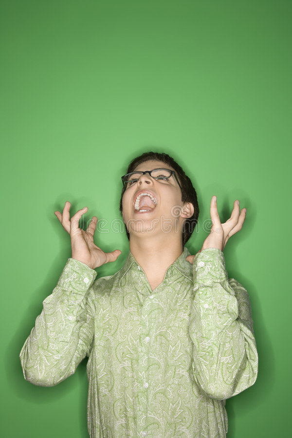 Teen boy screaming. Portrait of Caucasian teen boy screaming with hands beside ears in front of green background stock photography