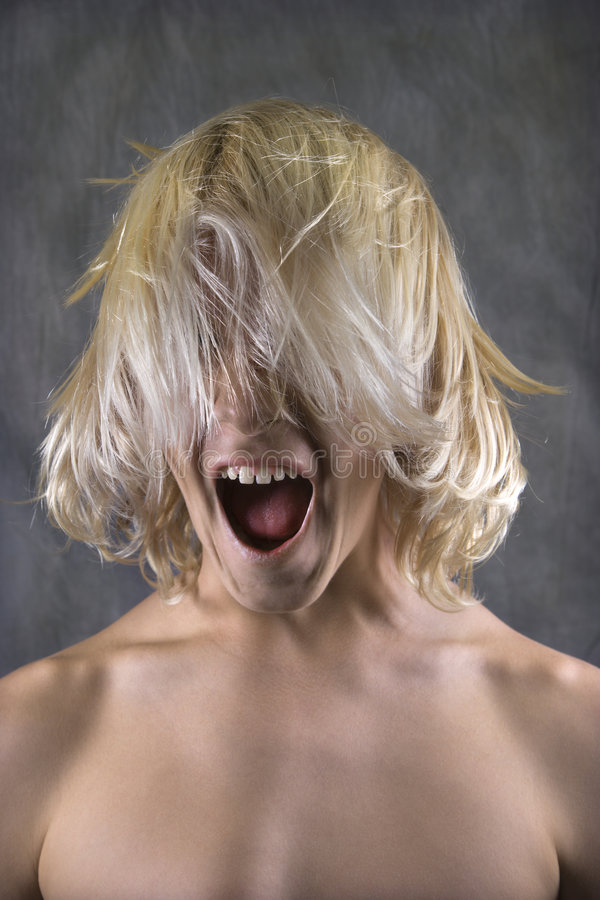 Teen boy screaming with hair in face. royalty free stock images
