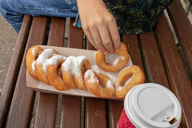 A teen boy sitting on a bench in park and eating beignet pastries, donuts and drinking coffee or tea from a takeaway box and cup, royalty free stock image