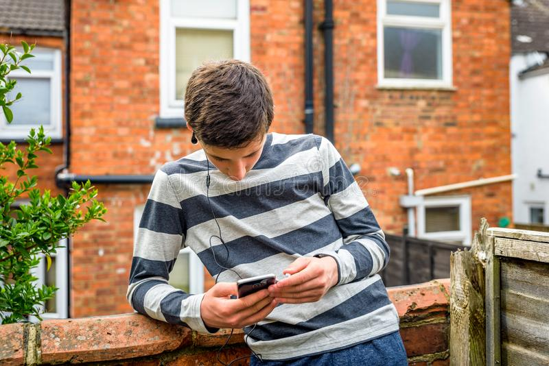 Teen boy with smart phone listening or talking while sitting in british backyard garden. teenager and social media. Concept royalty free stock photography
