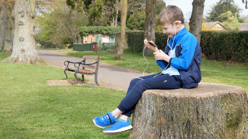 Teen boy with smart phone listening or talking while sitting on stump in british park. teenager and social media concept.  stock photos
