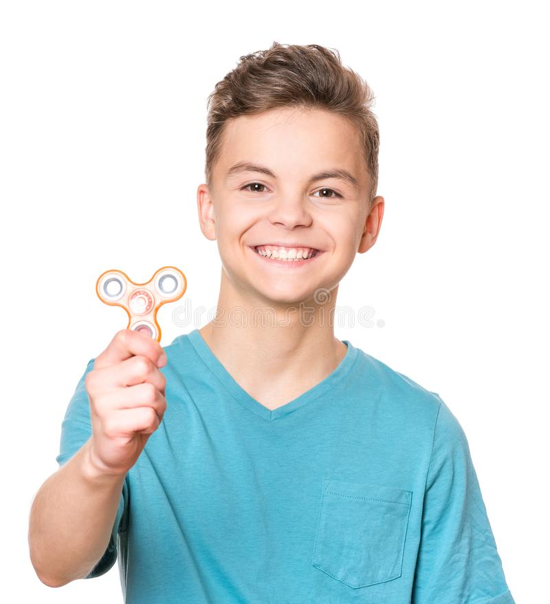 Teen boy with spinner toy. Young teen boy holding popular fidget spinner toy - close up portrait. Happy smiling child playing with Spinner, isolated on white stock photography