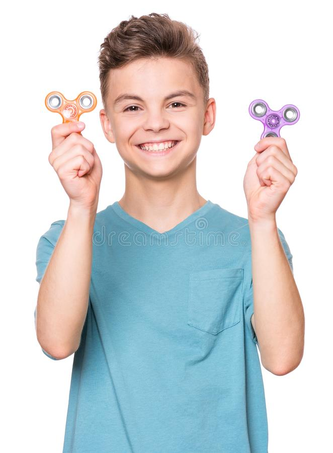 Teen boy with spinner. Young teen boy holding popular fidget spinner toy - close up portrait. Happy smiling child playing with Spinner, isolated on white royalty free stock photography