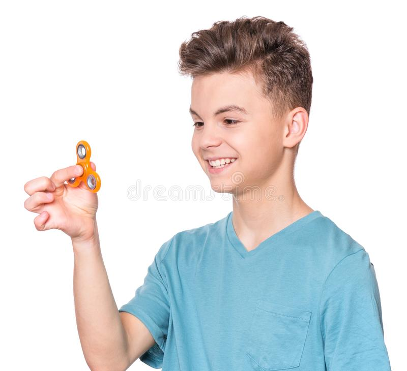 Teen boy with spinner. Young teen boy holding popular fidget spinner toy - close up portrait. Happy smiling child playing with Spinner, isolated on white royalty free stock photos