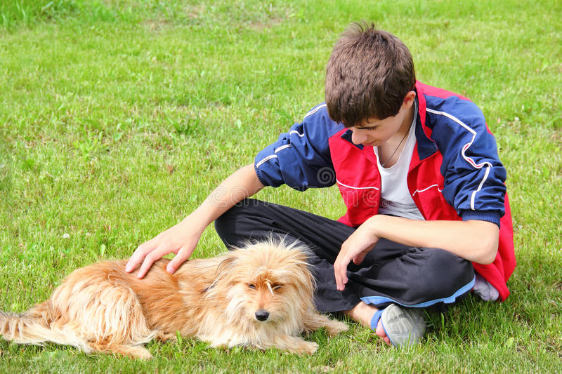 Teen boy stroking his dog. Sitting on the grass stock photo