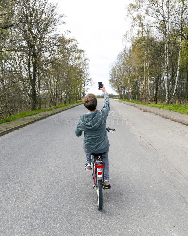Teen boy takes a selfie while cycling on the road royalty free stock images
