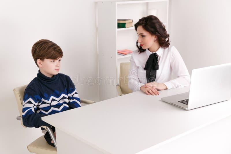 Teen boy talking to his therapist. Social worker and patient. Teen boy talking to his therapist. Social worker and patient royalty free stock images