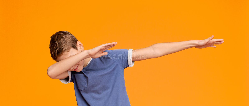 Teen boy throwing dab move, orange background. Teen boy throwing dab move, orange panorama background royalty free stock image