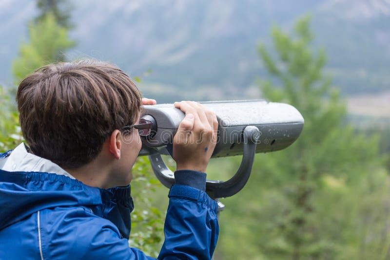 Teen boy using binoculars royalty free stock image