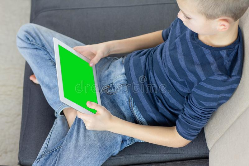 Teen boy using tablet pc with green screen while sitting on sofa at home. Close up of thumb scrolling up through touch screen stock photos