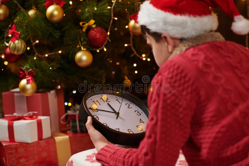 Teen boy waiting for Santa and watching the clock, lying indoor near decorated xmas tree with lights, dressed as Santa helper - royalty free stock photos