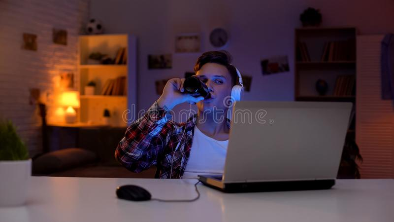 Teen boy watching movie on laptop and drinking beer, lack of parental control stock images
