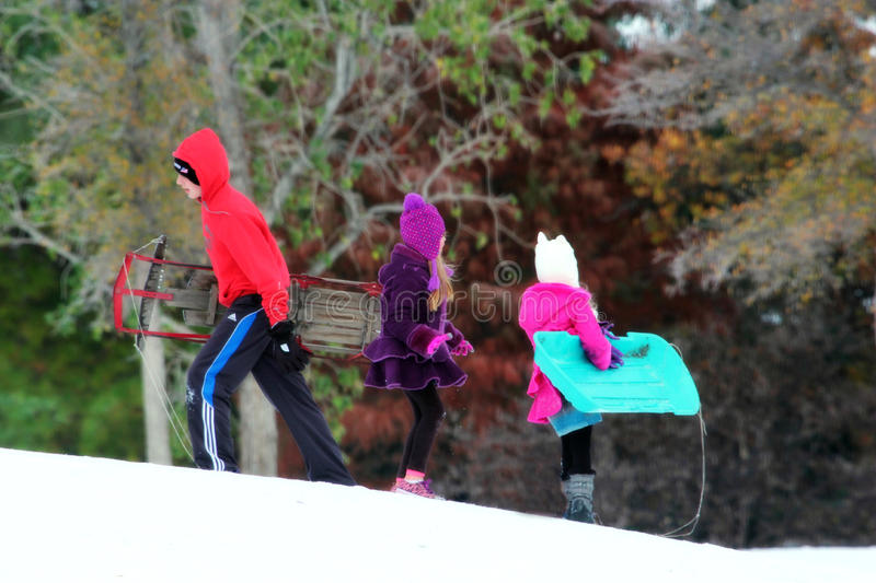 Teen Boy and Young Girls Carry Sleds On a Snowy Hill royalty free stock photos