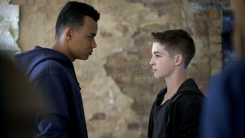 Teen boys arguing, conflict between school bully and geek, street violence royalty free stock photo