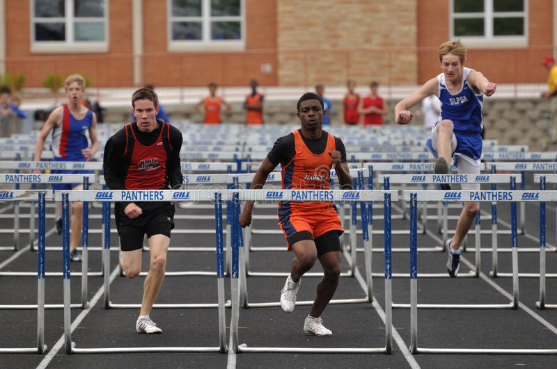 Teen Boys Competing in High School Hurdles Race royalty free stock photography