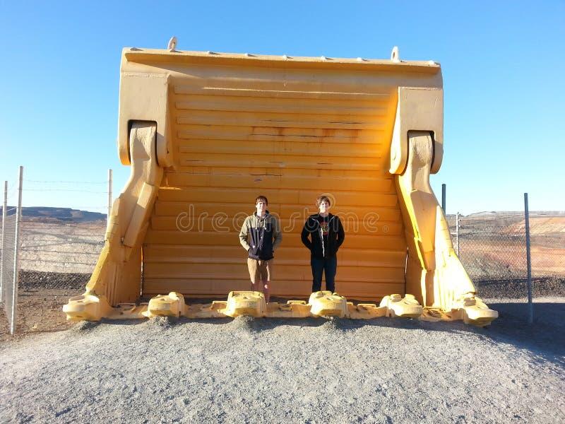 Teen Boys standing in huge mining excavator bucket royalty free stock images