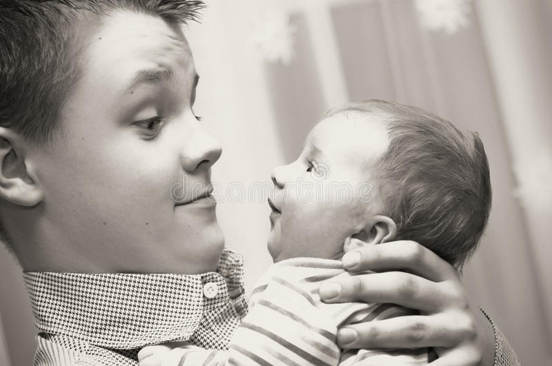 Teen brother with baby sister. Sepia toned image of teen brother holding his baby sister, funny faces royalty free stock image