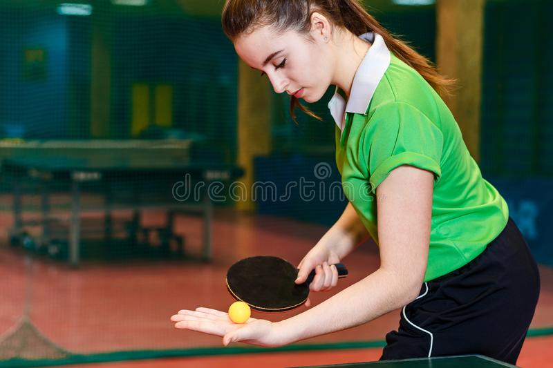 Teen brunette girl standing near a tennis table and preparing to serve the ball at a sports school. Fifteen-year-old teen brunette girl standing near a tennis stock photos