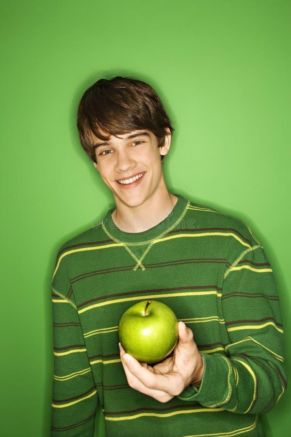 teen caucasian holding för äpplepojke fotografering för bildbyråer