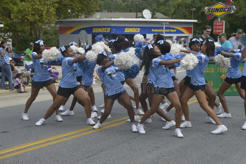 Teen cheerleaders perform at the labor day parade in Greenbelt, Maryland. Cheerleaders from Eleanor Roosevelt High school perform at the Labor Day parade in stock photography