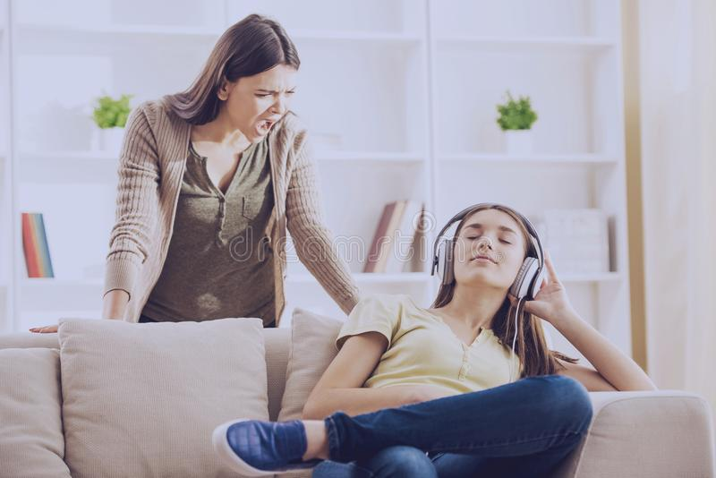 Teen closed ears with headphone while mom yells. At her.Problems between generations concept stock photo