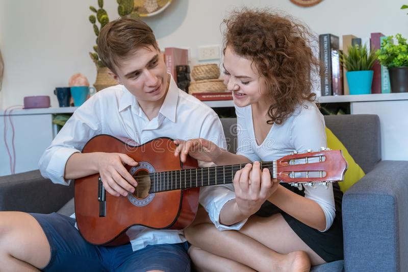 Teen couples are teasing each other during playing guitar royalty free stock photo