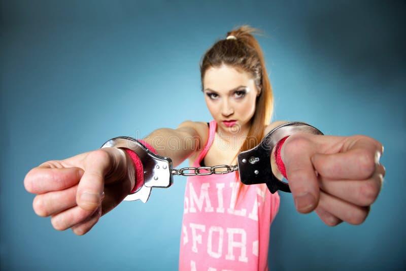 Teen crime - teenager girl in handcuffs. Studio shot blue background stock photos