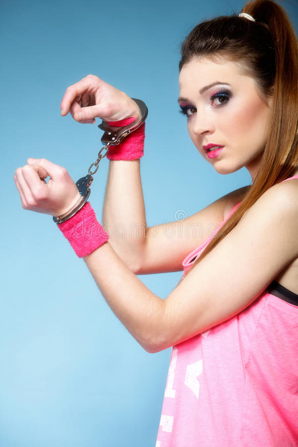 Teen crime - teenager girl in handcuffs. Studio shot blue background royalty free stock photos