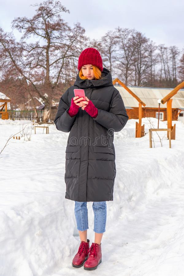 Teen cute girl in black down jacket, blue cropped jeans, burgundy hat, boots and fingerless gloves standing outdoor against winter. Rural landscape. Weekend at stock image
