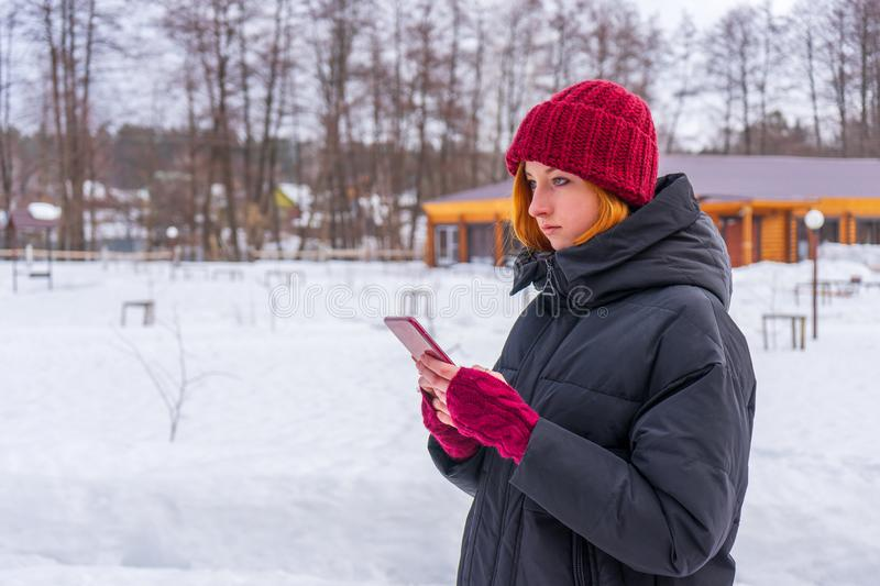 Teen cute girl in black down jacket, burgundy hat and fingerless gloves with smartphone in hands standing outdoor against winter. Rural landscape. Weekend at stock images