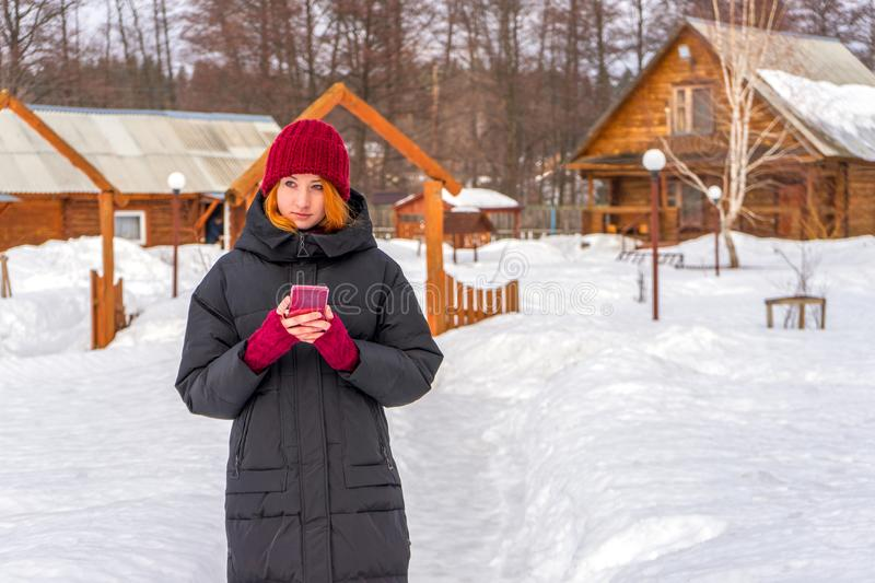Teen cute girl in black down jacket, burgundy hat and fingerless gloves with smartphone in hands standing outdoor against winter. Rural landscape. Weekend at stock photography