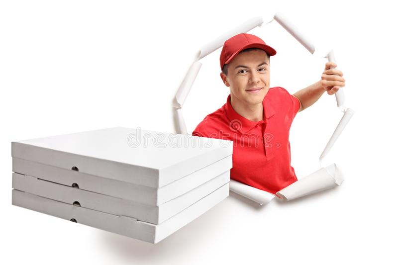 Teen delivery boy breaking through paper royalty free stock photography