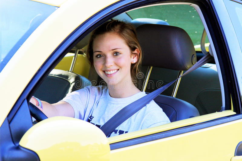 Teen Driver. Female teen driver sitting in car with seat belt on and smiling