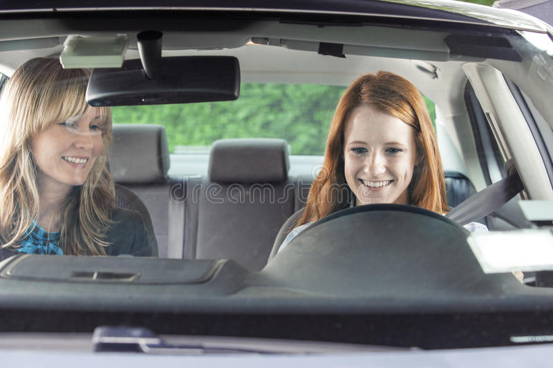 Teen driver with instructor. Teenager in car with driving instructor stock images