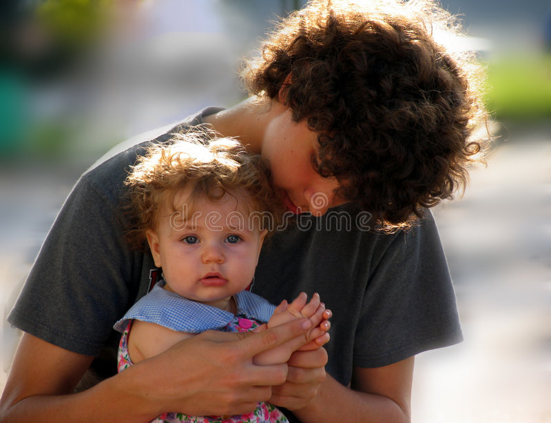 Teen Fatherhood. Teenage boy with a baby(actually it's his sister royalty free stock photo