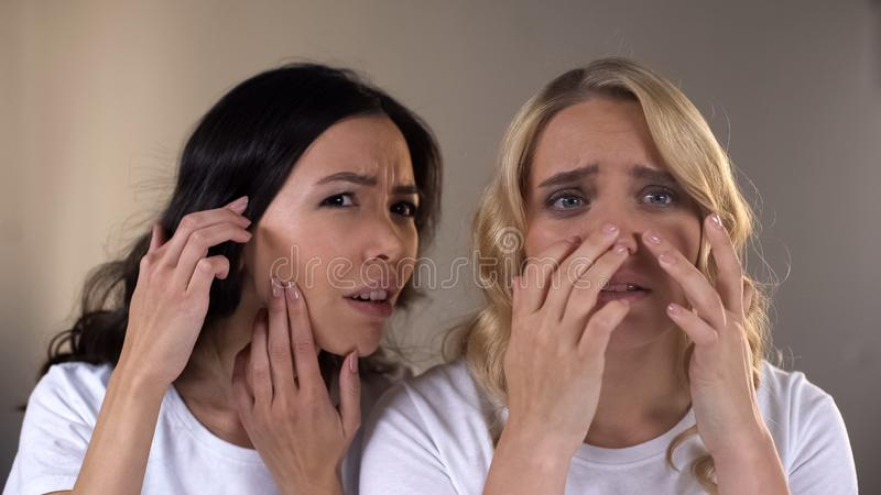 Teen female friends looking in mirror, noticing pimples on face, problem skin. Stock photo royalty free stock images