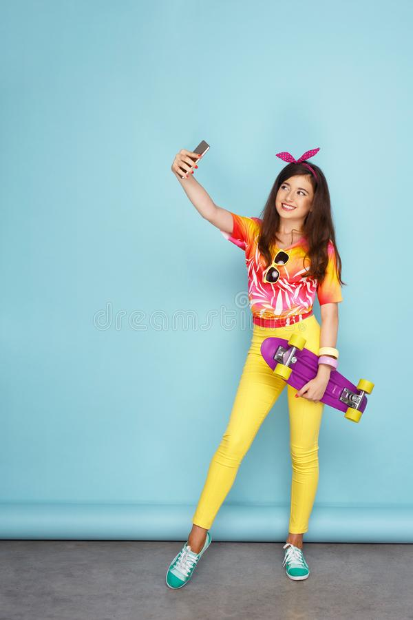 A teen female model holding a skateboard, doing selfie in studio with her smartphone, over blue background. royalty free stock photo