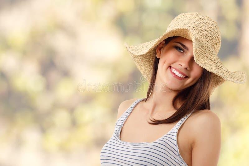 Teen flicka för sommar som är gladlynt i sugrörhatt arkivfoton