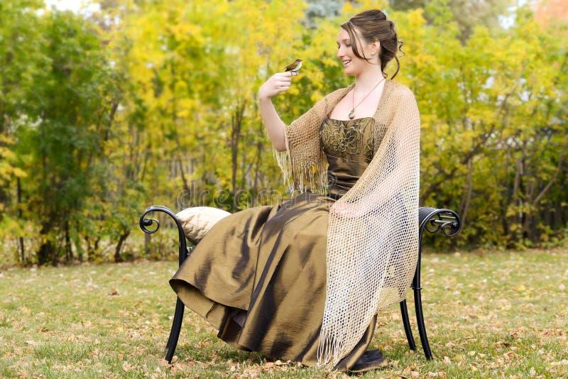 Teen flicka i trädgård med steglitsfågeln på fingret royaltyfri fotografi