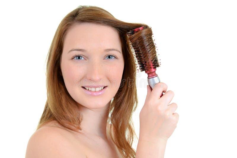 Teen flicka som krullar henne hår royaltyfri foto