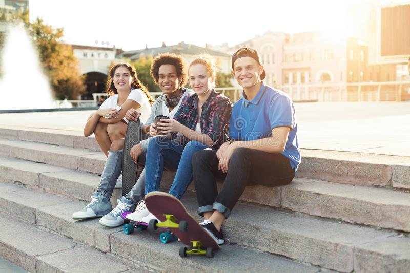 Teen friends company sitting outdoor, spending summer together stock photography