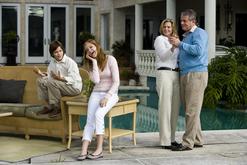 Teen girl amused by parents dancing stock photos
