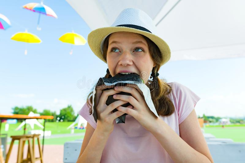 Teen girl with an appetite eats black fast food burger. Summer street cafe, recreation area, city park background. Teen girl with an appetite eats black fast stock image