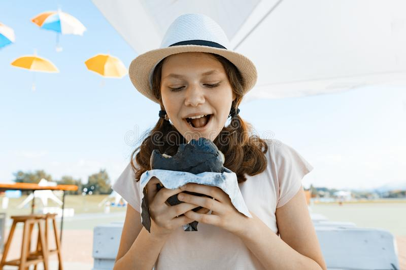 Teen girl with an appetite eats black fast food burger. Summer street cafe, recreation area, city park background.  royalty free stock image