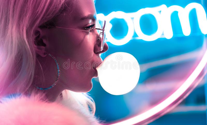 Teen girl blowing bubble gum illuminated with street neon blue pink sign. Young fashion teen girl in fur glasses blowing bubble gum illuminated with street neon stock image