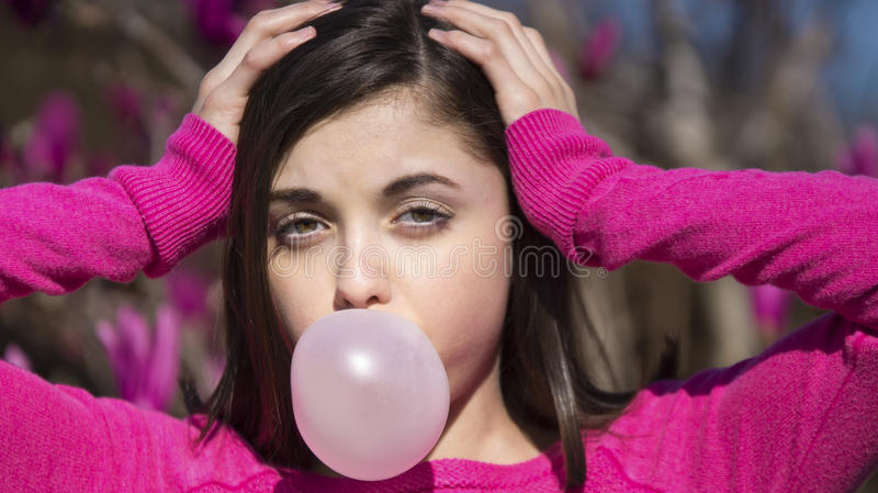 Teen girl blowing bubblegum bubble stock photo
