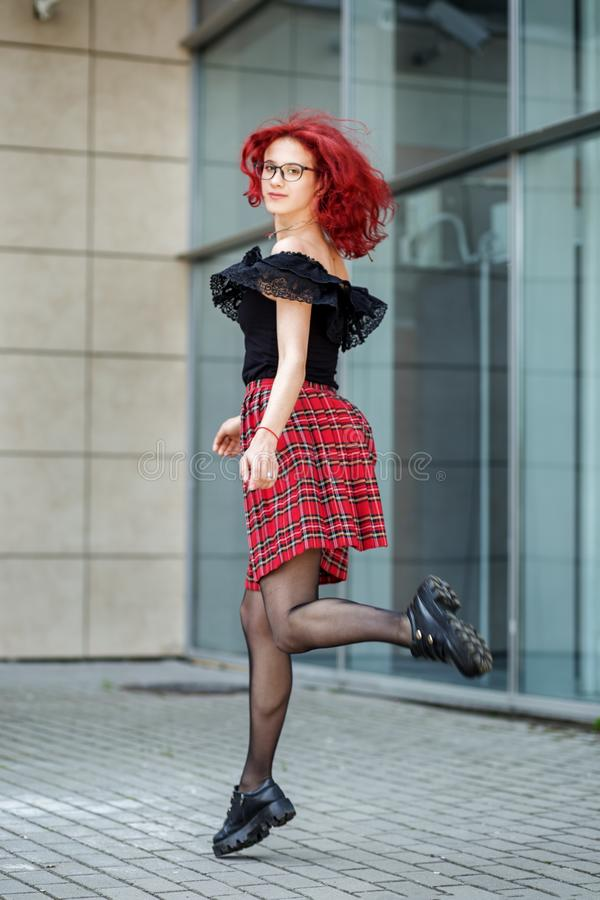Teen girl bounces on the street. Red hair. Concept of lifestyle, urban, travel, fashion stock photography