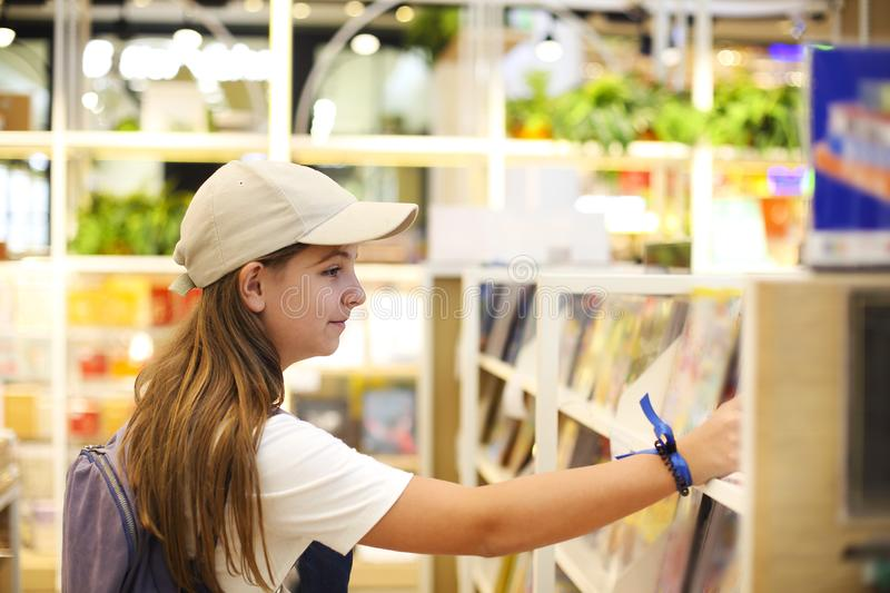 Teen girl choosing the book in book store, education concept royalty free stock image